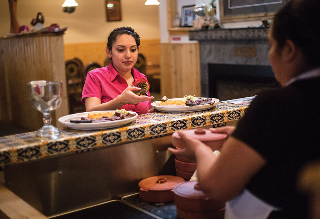 A waitress at El Abuelito picks up fresh tortillas to accompany diners' entrees.