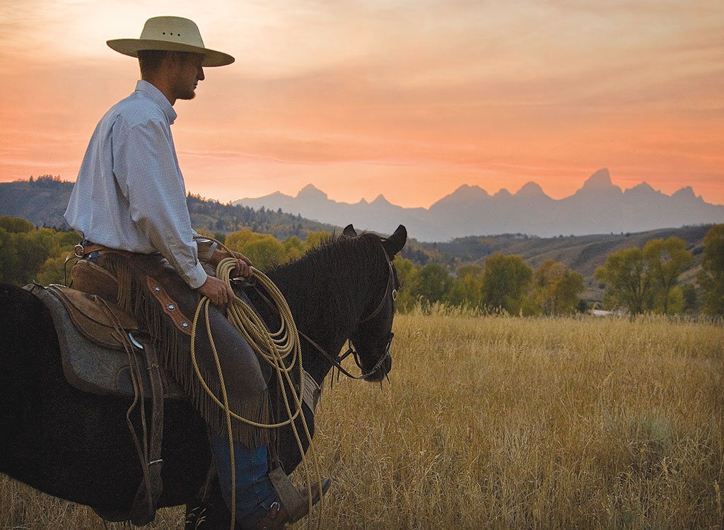 Joe Ferguson, a wrangler at the Gros Ventre River Ranch, looks across the valley to the Tetons at the end of a summer day.