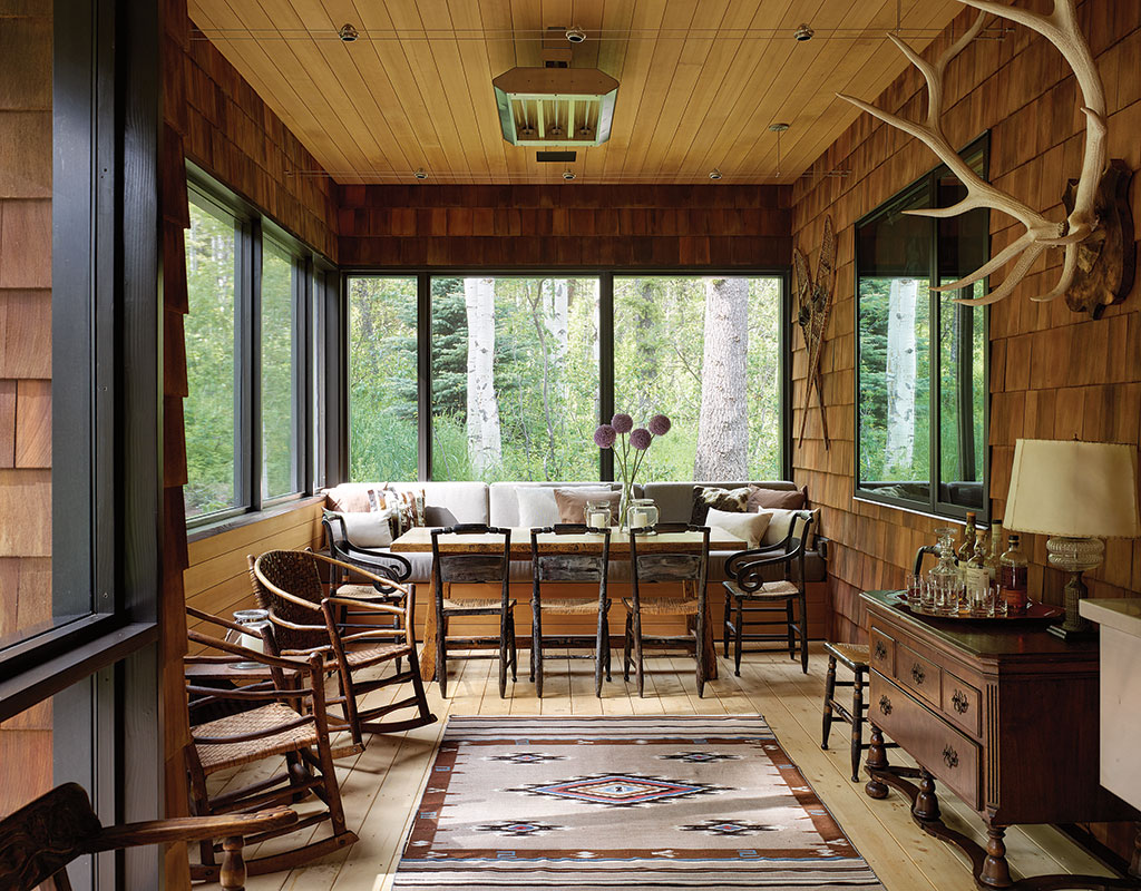 The screened-in porch at the home of Jackson architect John Carney is oriented to capture the setting sun and create a cozy, intimate space for reading, cooking, and entertaining.