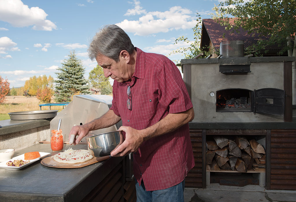 Dan Mei prepares a pizza on the porch of his home north of Jackson. The family's pizza oven was imported from Italy by a friend of the Arizona restaurateur.