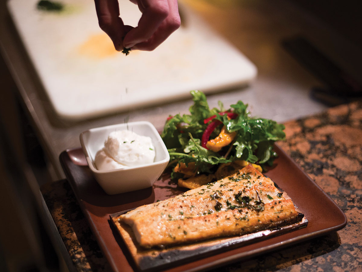Sous chef Vincent Affinito puts the finishing touches on the cedar-plank trout with poached eggs, heirloom tomatoes, and sweet onion kale salad at Four Seasons' Westbank Grill.