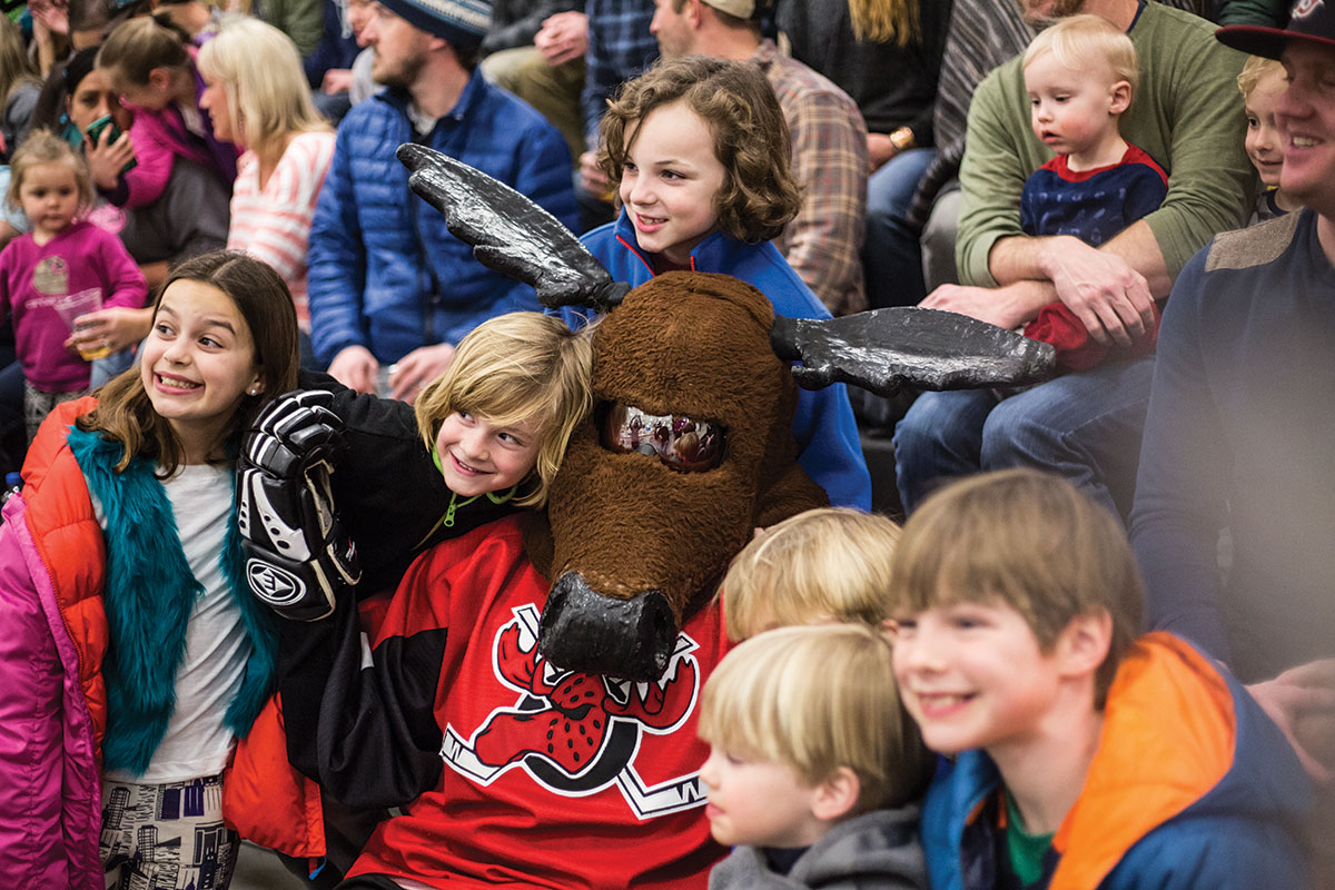 Knuckles takes time off from pumping up the crowd to pose for a picture with a group of young Moose Hockey fans.